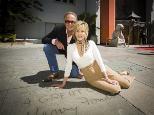 Jane and Peter Fonda sit next to their father's hand and foot prints at Grauman's Chinese Theatre.